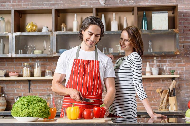 Blije echtgenoot en vrouw die voedsel in keuken voorbereiden stock foto