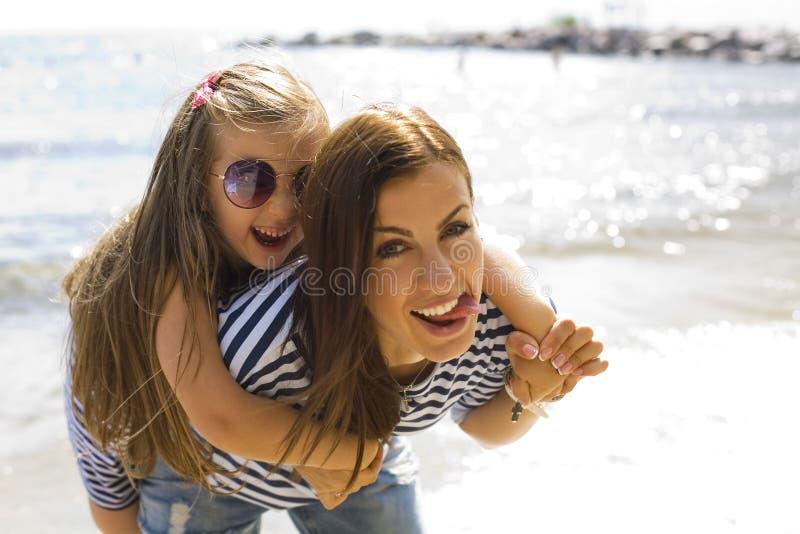 Blije en positieve moeder en dochter dichtbij het overzees royalty-vrije stock fotografie
