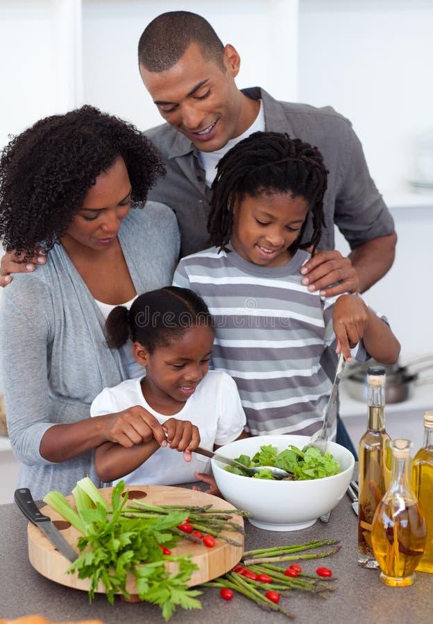 Blije familie die diner in de keuken voorbereidt stock afbeeldingen