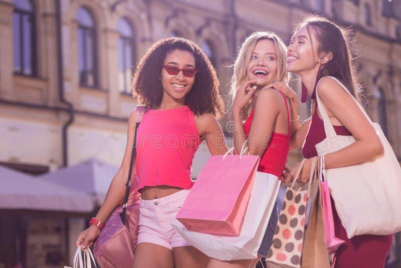 Blije gelukkige jonge vrouwen die hun het winkelen zakken houden stock foto's