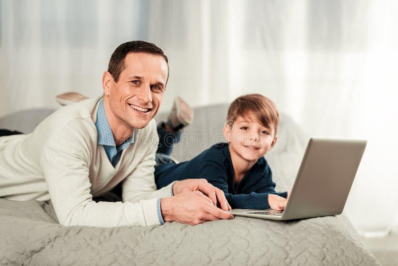 Blije gelukkige vader en zoon die u bekijken stock fotografie
