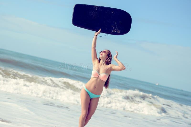 Blije gelukkige vrolijk van het surfermeisje bij oceaanstrandwater stock fotografie