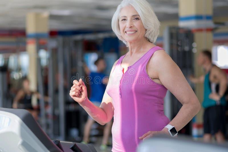 Blije glimlachende hogere vrouw die op tredmolen uitoefenen stock foto