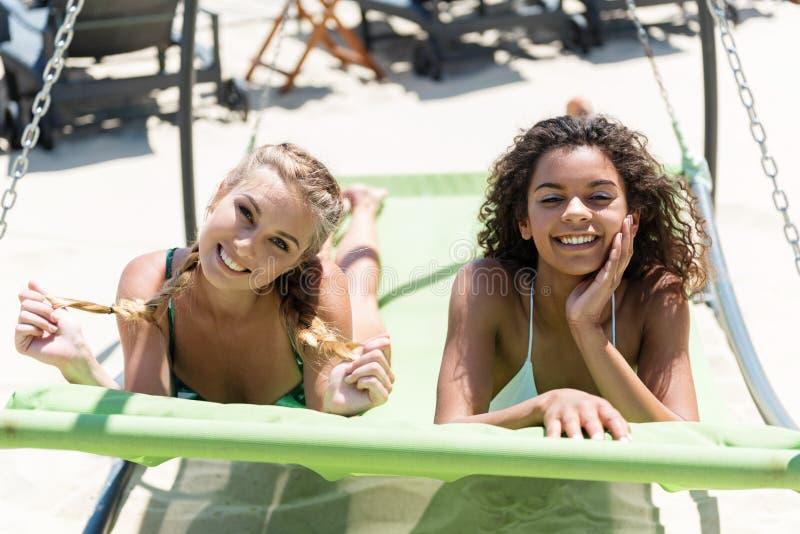 Blije jeugdige meisjes die op overzees ontspannen stock afbeeldingen