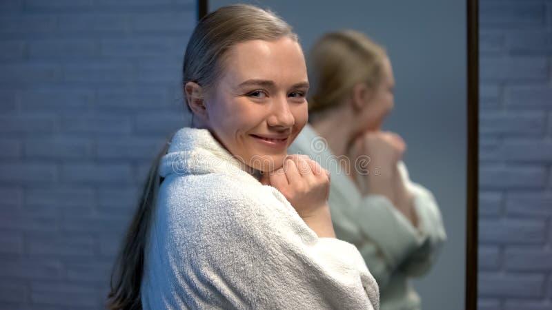 Blije jonge dame die in badjas aan camera na kuuroordprocedures glimlachen, ontspanning royalty-vrije stock foto