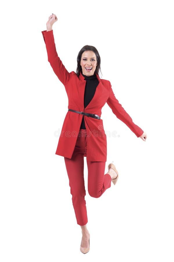 Blije jonge elegante aantrekkelijke bedrijfsvrouw in rood formeel kostuum het vieren succes stock afbeelding