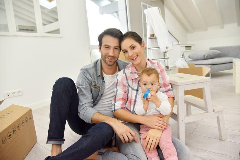 Blije jonge familie die zich in nieuw huis bewegen stock foto's