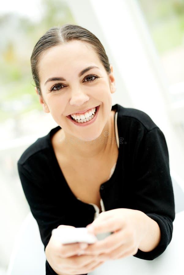 Blije jonge vrouw die bij de camera glimlachen stock afbeeldingen