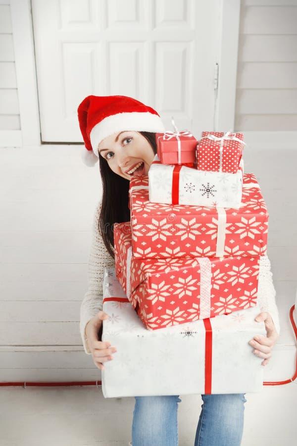 Blije jonge vrouw die een stapel van de dozen van de Kerstmisgift houden stock afbeelding