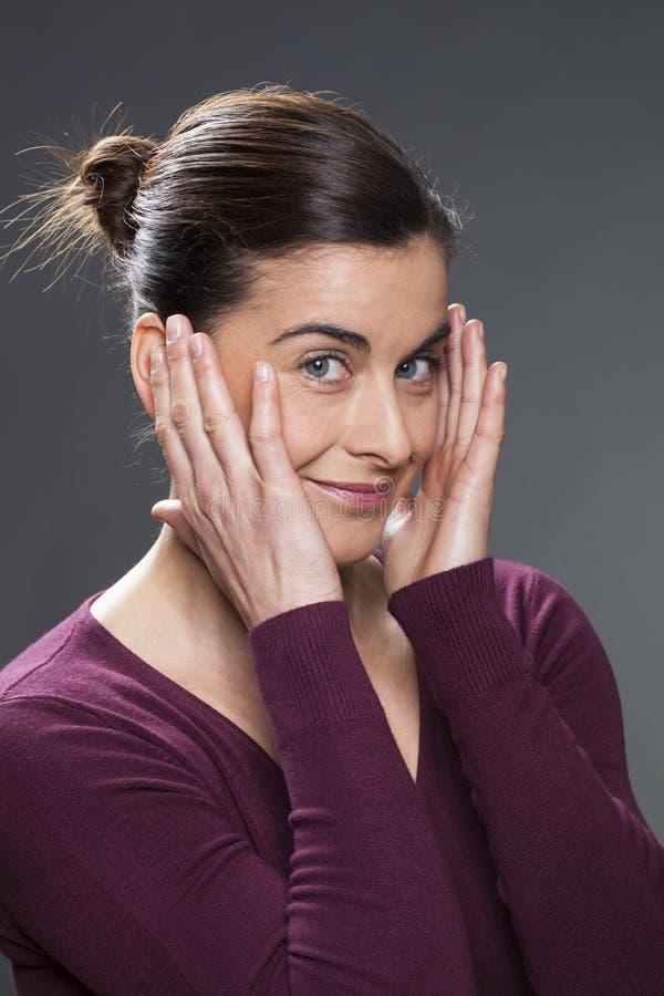 Blije jonge vrouw die haar tempels voor huid het gladmaken masseren stock foto's