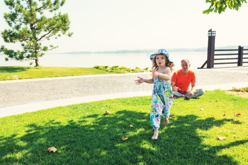 Blije kleine dochterspelen met haar vader in het park stock fotografie