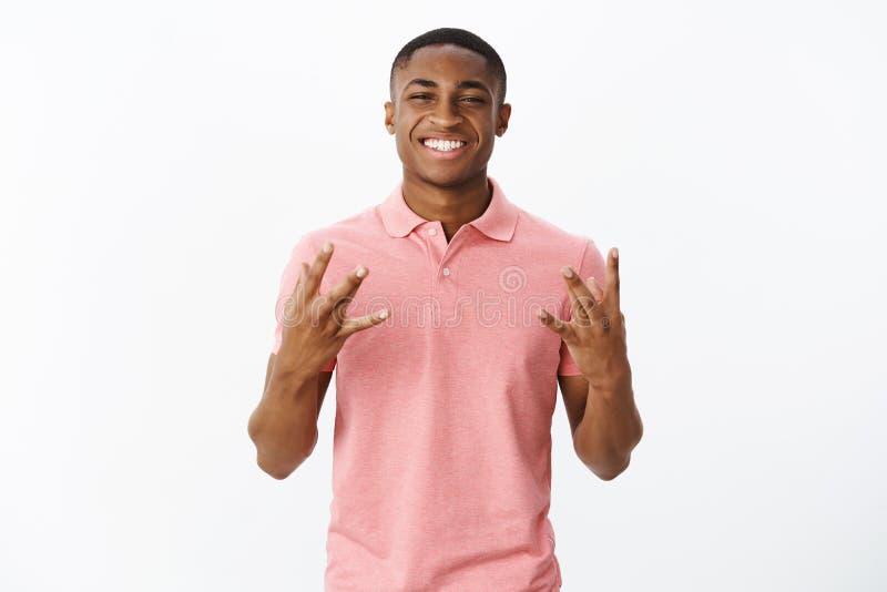 Blije knappe jonge Afrikaanse Amerikaanse vriend in roze polooverhemd vingers kruisen en zelf-tevreden glimlachen die royalty-vrije stock fotografie
