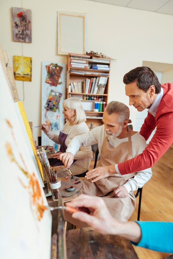 Blije kunstenaar die bejaarde in het schilderen van studio helpen royalty-vrije stock afbeeldingen