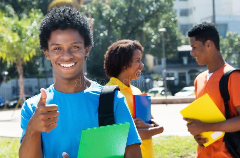 Blije lachende Afrikaanse Amerikaanse mannelijke student die duim op w tonen stock foto