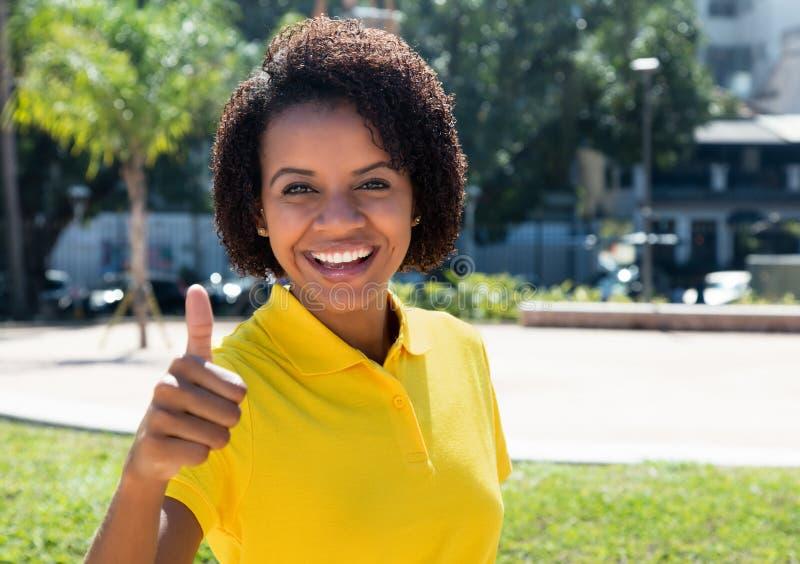 Blije lachende Afrikaanse Amerikaanse vrouw die duim tonen stock fotografie