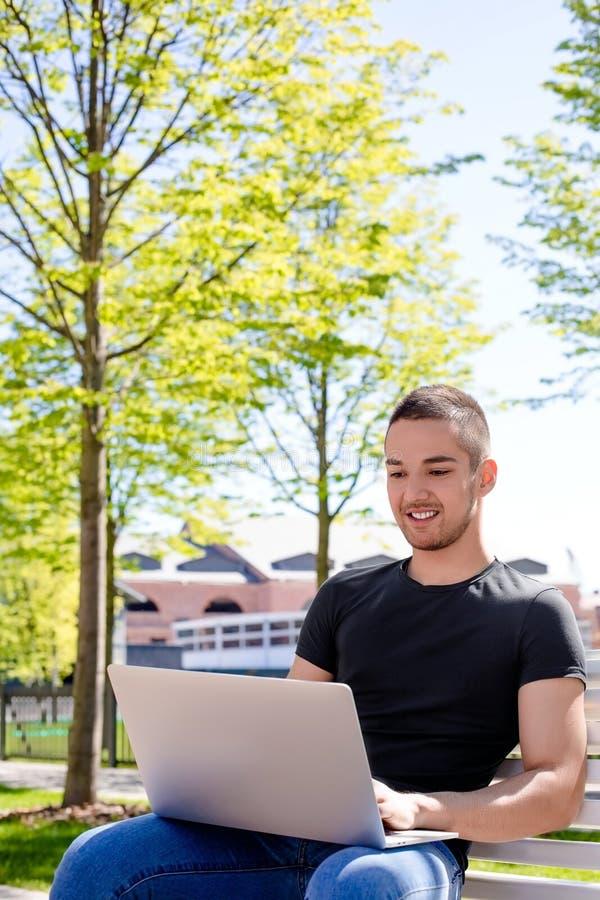 Blije mannelijke universitaire student die online onderwijs via netbook hebben, die op een campus zitten royalty-vrije stock foto