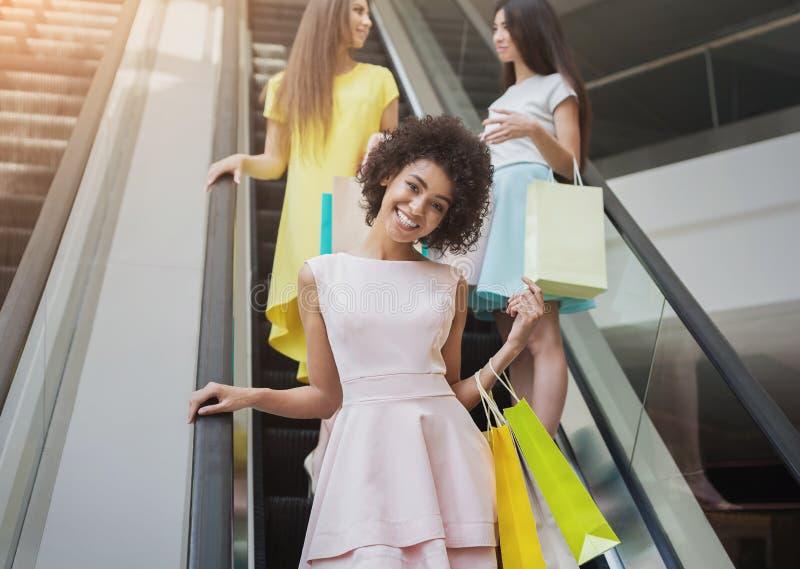 Blije meisjes op roltrap in winkelcomplex royalty-vrije stock afbeelding