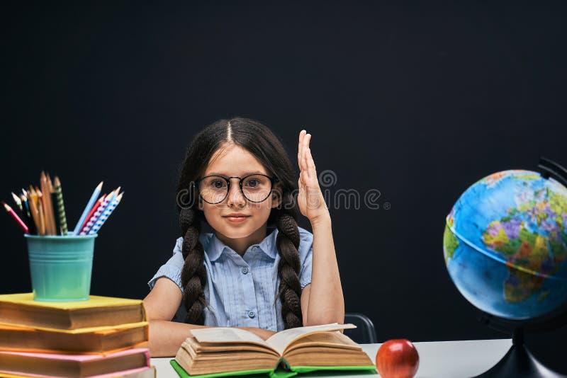 Blije meisjezitting bij de lijst met potloden en boekenhandboeken Gelukkige kindleerling die thuiswerk doen bij de lijst royalty-vrije stock foto's