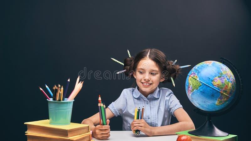 Blije meisjezitting bij de lijst met potloden en handboeken Gelukkige kindleerling die thuiswerk doen bij de lijst stock foto's