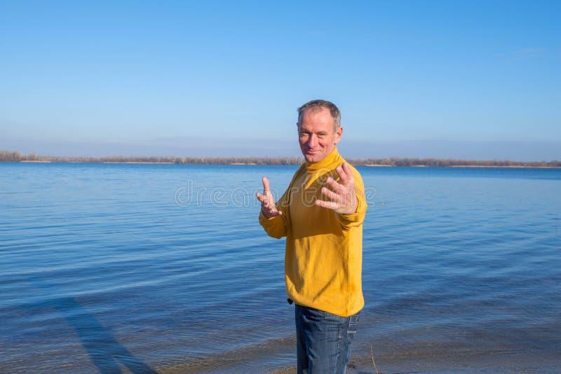 Blije mens, die ontspannend op het strand, lachen terloops dragen royalty-vrije stock afbeeldingen