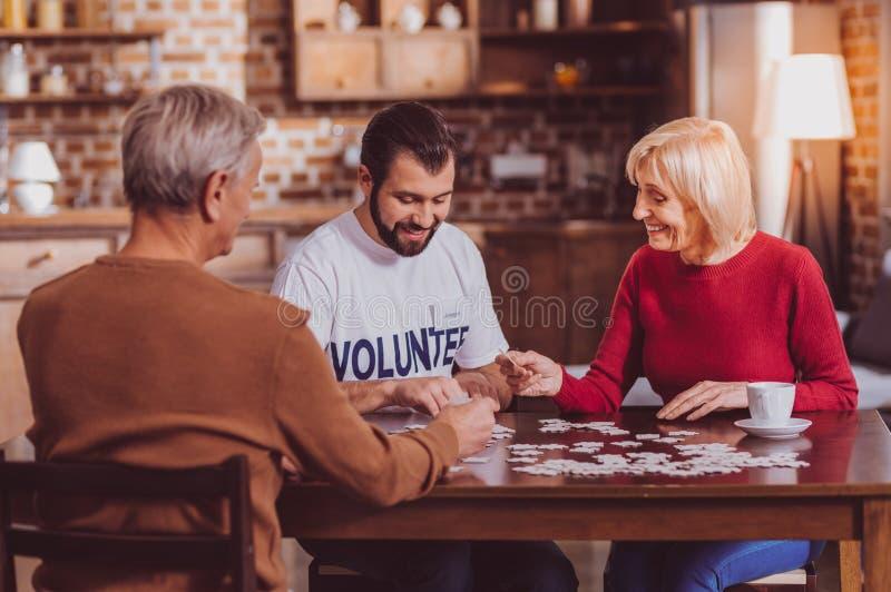 Blije mens die raadsels samen met gepensioneerden zetten stock foto