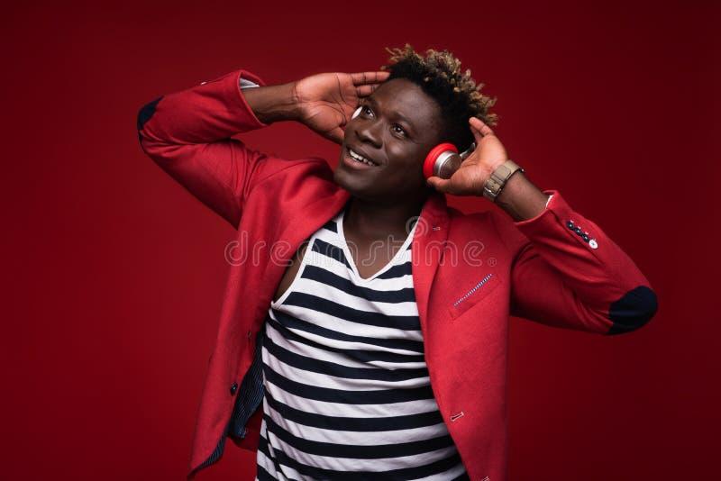 Blije mens het luisteren muziek op rode achtergrond stock afbeelding