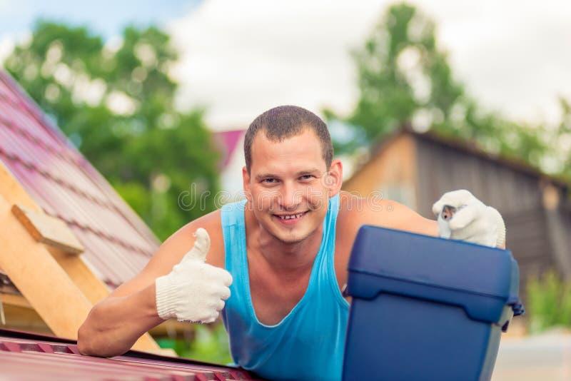blije mens met toolbox op het dak van het huis tijdens royalty-vrije stock afbeelding