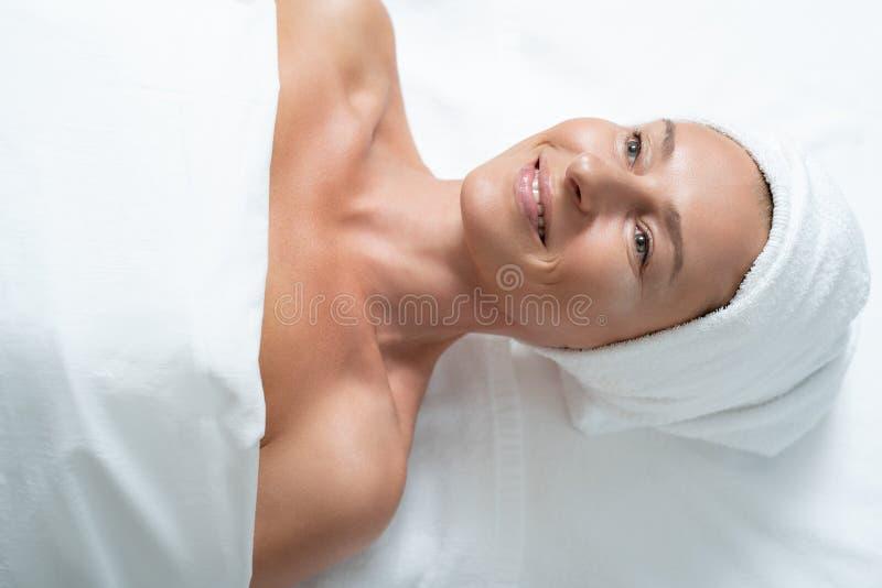 Blije midden oude vrouw die op massagelijst liggen royalty-vrije stock fotografie