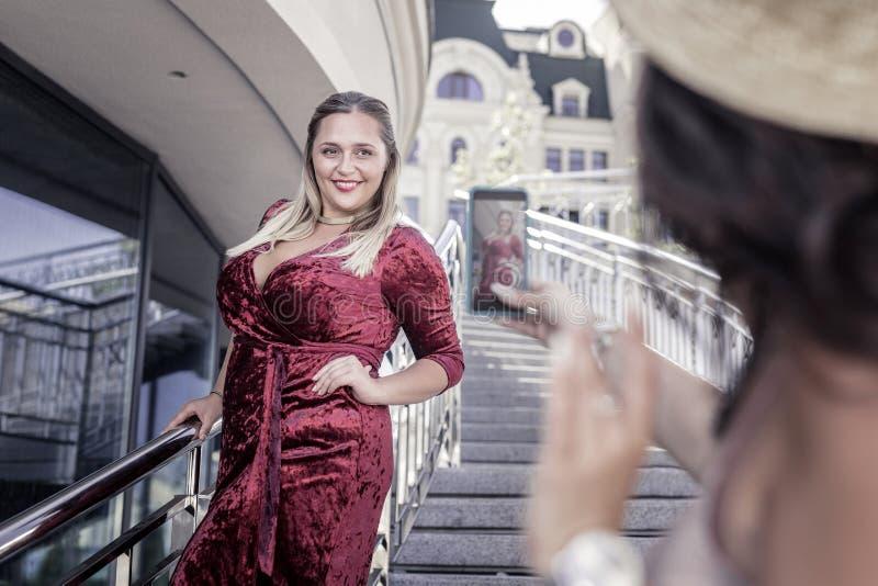 Blije mollige vrouw die een rode fluweelkleding dragen royalty-vrije stock foto