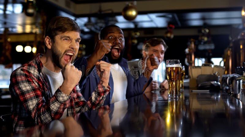 Blije multiraciale vrienden die voor favoriet team in bar, het vieren doel toejuichen stock fotografie