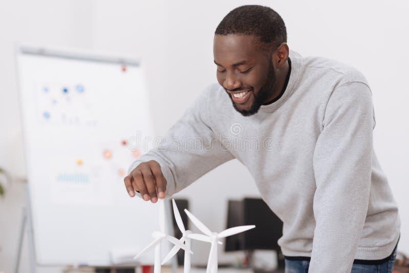 Blije opgetogen mens die de windmolenmodellen bekijken stock fotografie