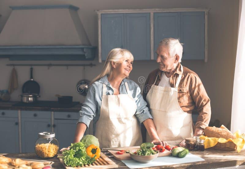 Blije oude man en vrouw die diner in keuken voorbereiden stock afbeeldingen