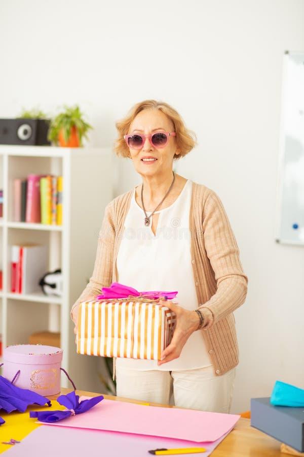 Blije oude vrouw die een grote giftdoos houden stock afbeelding