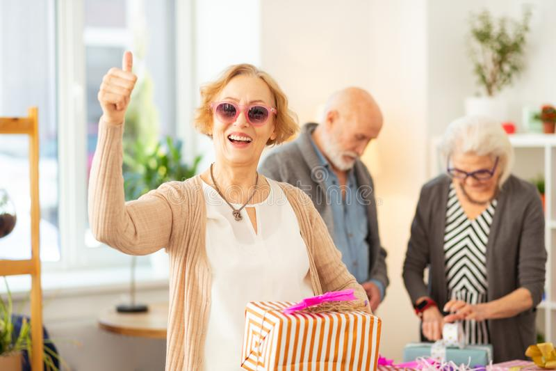 Blije oude vrouw die een huidige doos in haar handen houden royalty-vrije stock foto