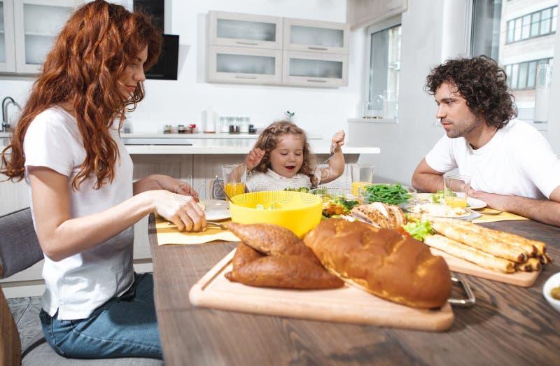 Blije ouders en dochter die gezond voedsel in keuken eten royalty-vrije stock fotografie