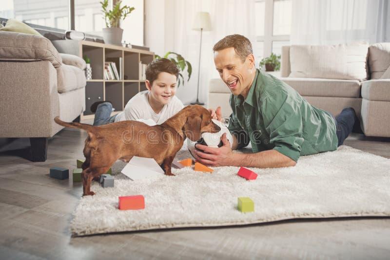 Blije papa en zoons speelvoetbal met puppy stock afbeelding