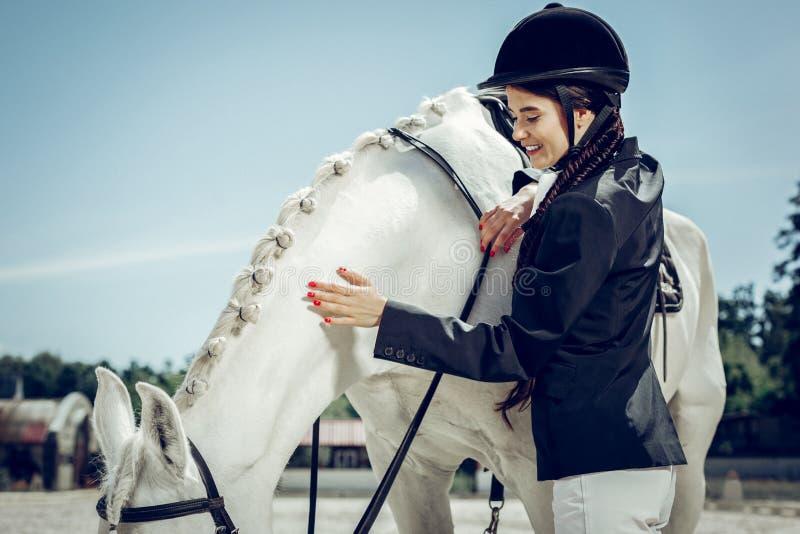 Blije positieve jonge vrouw die om haar paard geven stock afbeeldingen