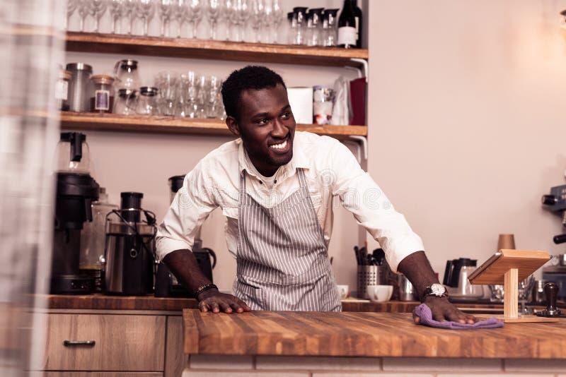 Blije positieve mens die de teller in de koffie schoonmaken royalty-vrije stock fotografie
