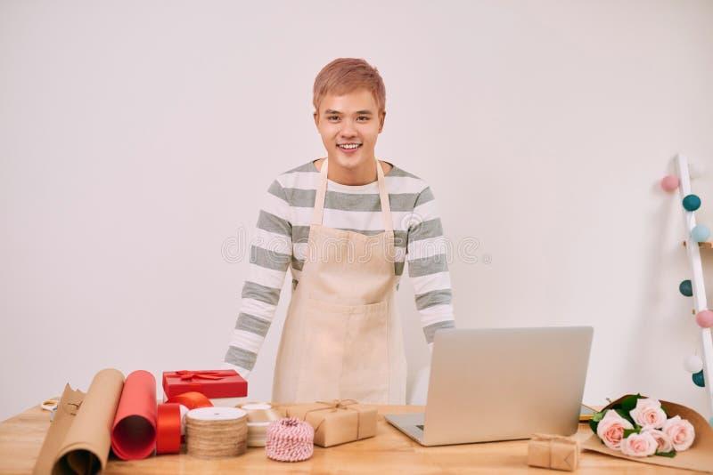 Blije prettige mannelijke verkoper die met laptop in een giftwinkel werken stock foto