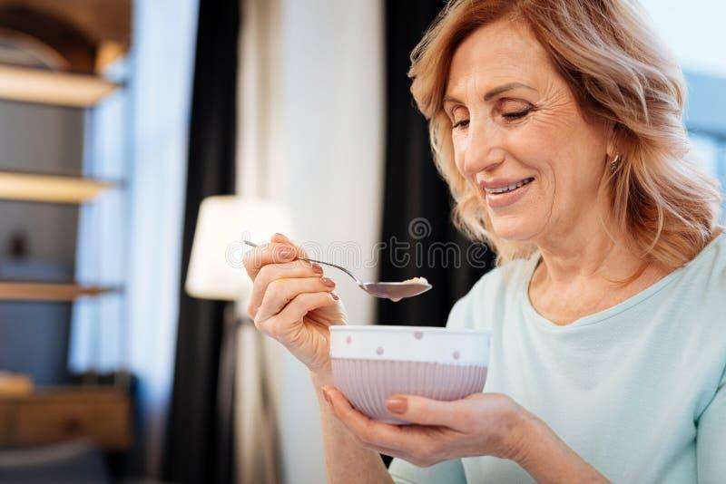 Blije rijpe dame die in comfortabele uitrusting ochtendhavermoutpap eten stock afbeelding