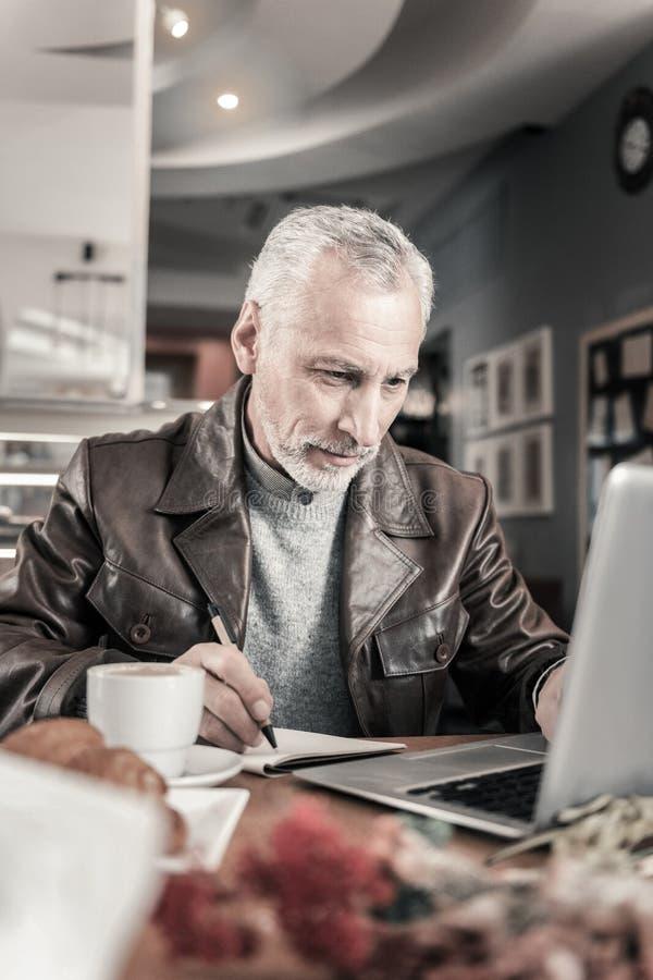 Blije rijpe mens die aan afstand bij computer werken stock foto's