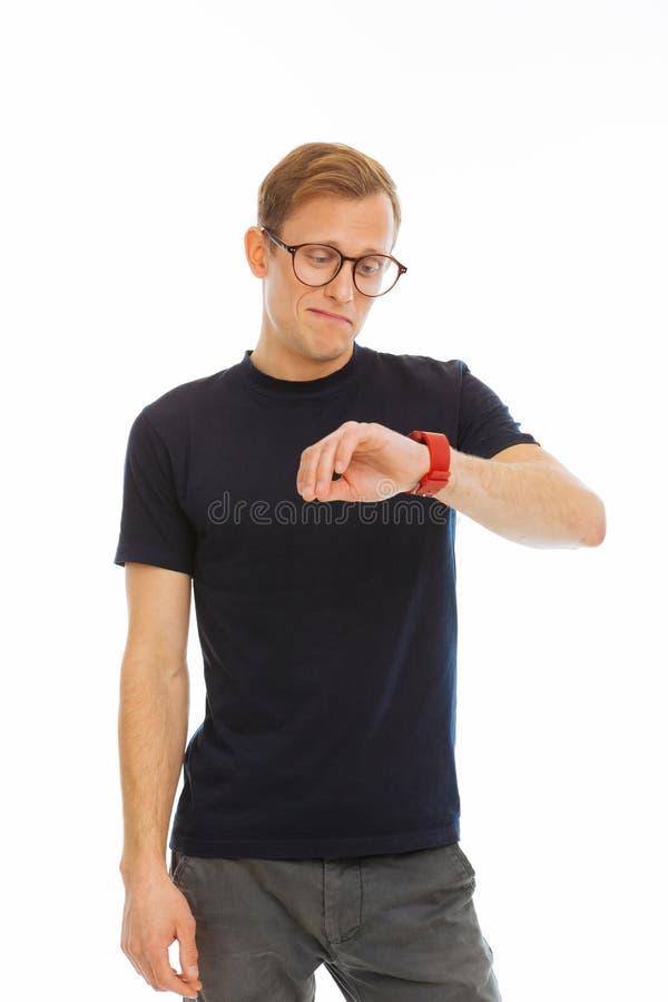 Blije slimme mens die zijn smartwatch bekijken stock fotografie