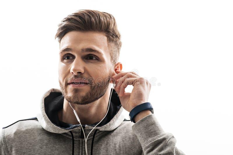 Blije sportieve mens die aan oortelefoons luisteren stock foto's