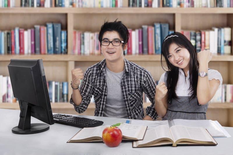 Blije studenten die succes 3 uitdrukken stock afbeeldingen