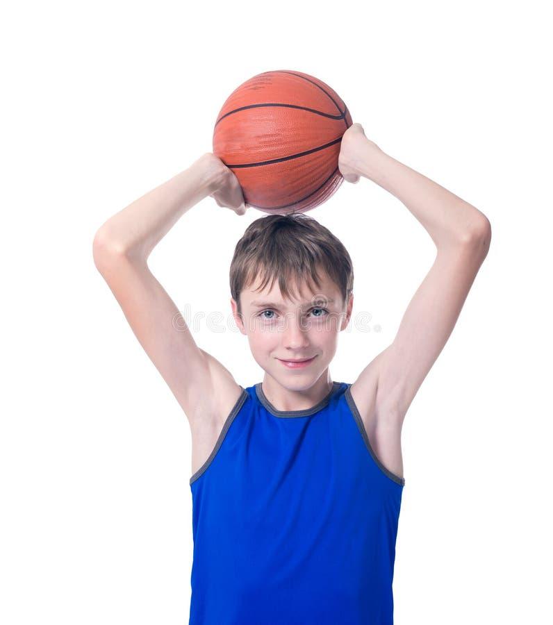 Blije tiener die een bal voor basketbal over zijn hoofd houden Is royalty-vrije stock fotografie