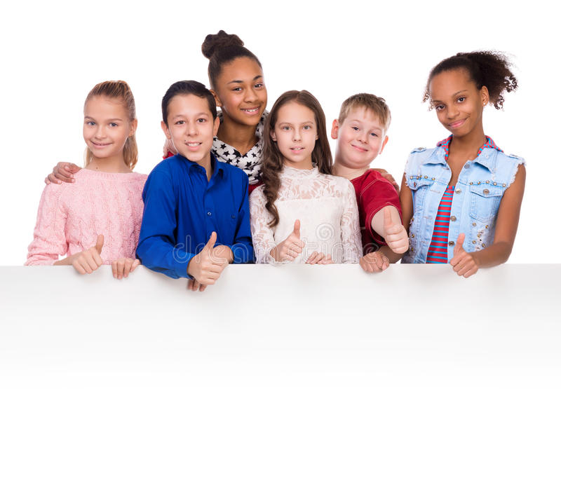 Blije tieners met duimen op het houden van een lege spatie stock afbeeldingen