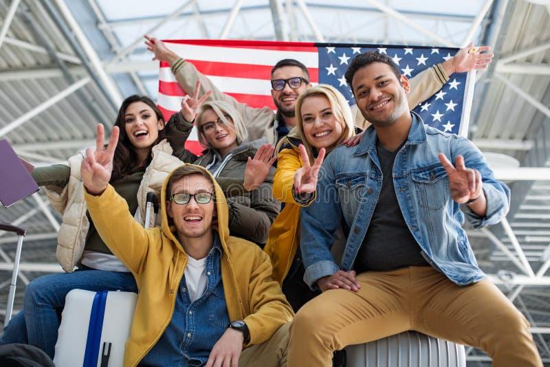 Blije toeristen die Amerikaanse vlag in de terminal aantonen royalty-vrije stock foto