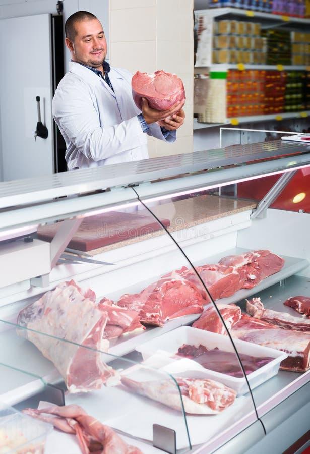 Blije verkoper dichtbij vertoning met gekoeld vlees stock foto