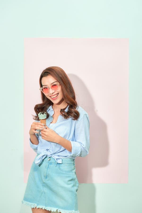 Blije verrukkelijke jonge Aziatische vrouw die smakelijk roomijs, tribunes op lichtrose achtergrond houden royalty-vrije stock afbeeldingen