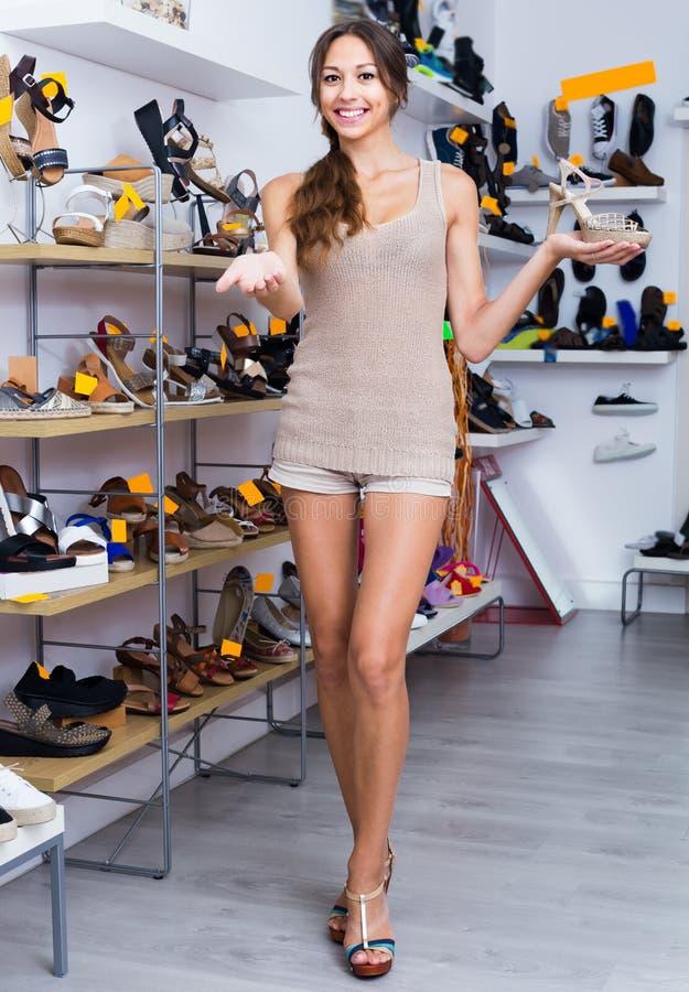 Blije volwassen vrouw die zich met gekozen schoen bevinden stock afbeelding